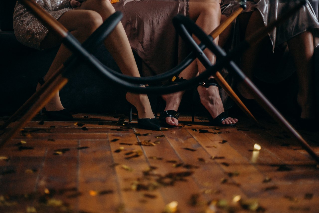 Pés com salto alto debaixo da mesa