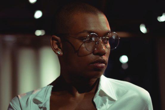 Homem negro de óculos olhando para o lado